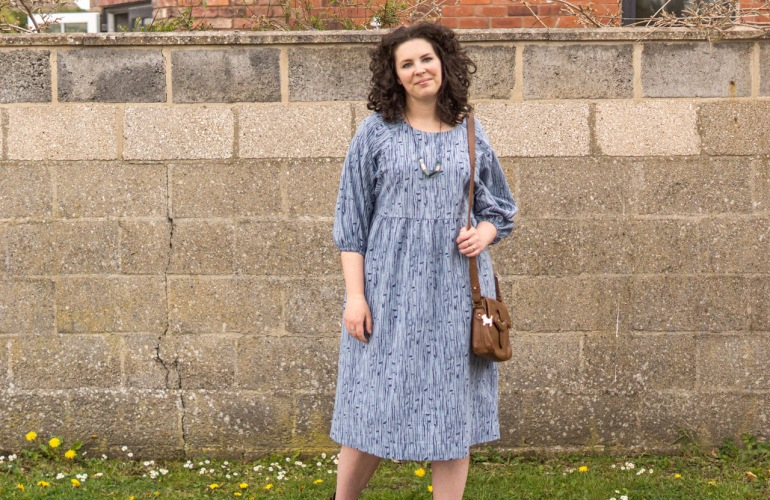 Image of a white woman with dark brown hair, wearing a blue linen dress made from the Style Arc Hope sewing pattern